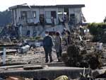 Pessoas caminham por entre os escombros em Minamisoma, Fukushima