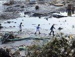 Um grupo de pessoas caminha sobre escombros em Minamisanrikucho.