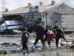 Moradores circulam por ruas destruídas em Tagajo, na província de Miyagi