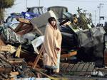 Enrolada em cobertor, menina japonesa observou a destruição deixada pelo tsunami em Ishinomaki, na província de Miyagi