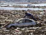 Morador procura por itens no carro de sua mãe em meio a destroços na cidade de Sendai