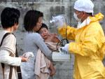 Técnico verificou a radiação de bebê após descontaminação em Fukushima, dia 14 de março