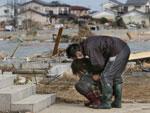 Homem amparou mulher na cidade de Watari, em Miyagi, três dias após o terremoto de 9 graus na escala Richter