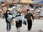 Sobreviventes carregam os bens que conseguiram recuperar de suas casas destruídas pelo terremoto seguido de tsunami na cidade de Ofunato