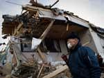 Com máscara, morador passa por área devastada em Kesennuma, na província de Miyagi