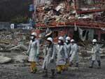 Socorristas procuram por vítimas nos escombros da cidade de Kesennuma, em Miyagi