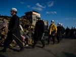 Socorristas caminhavam entre casas destruídas pelo terremoto e pelo tsunami na cidade de Rikuzentakata