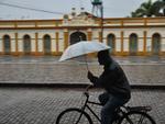 Mesmo inadequado para uso na bicicleta, o guarda-chuva proteje contra a chuva, em Pelotas/RS