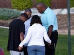 Enquanto aguarda informações, um pequeno grupo reza pelas vítimas do atirador que invadiu uma sessão de cinema no estado do Colorado, Estados Unidos, e matou pelo menos 12 pessoas