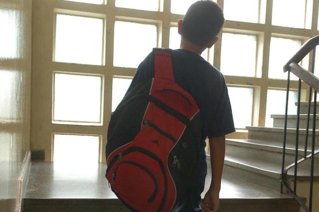 Mochila infaltil sendo usada por criança. Mochila com sobrepeso sendo carregada com uma alça apenas.