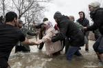 Retidos na fronteira da Macedônia, refugiados fazem travessia por rio