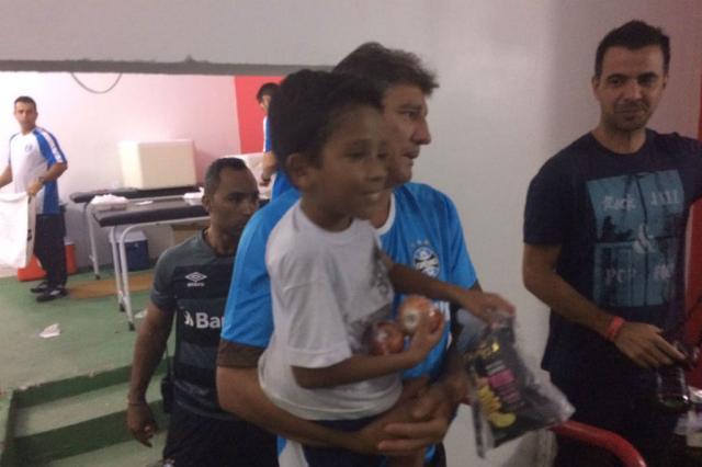 No colo de Renato, garoto com doença rara visita vestiário gremista em Pelotas José Alberto Andrade / Rádio Gaúcha/Rádio Gaúcha