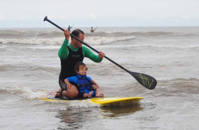 Menino de dois anos surfa com o pai na Praia do Cassino Pablo Bech, Divulgação /
